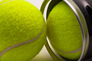 Yellow tennis balls out of black container