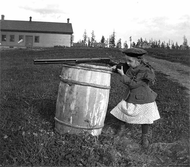 Miriam Kiehl shooting over a barrel, probably at Fort Lawton