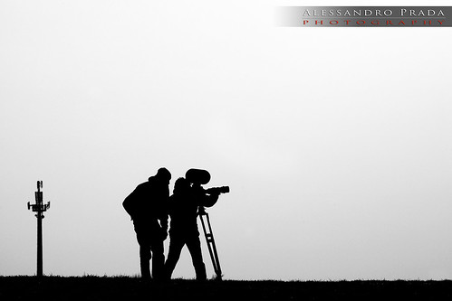 Long shot, black and white image of two men with a video camera.