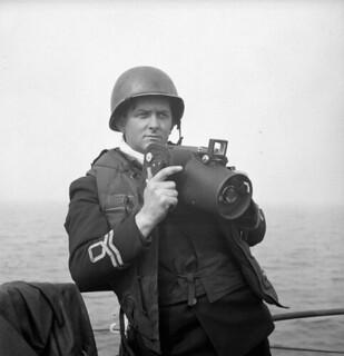 Lieutenant Gilbert A. Milne of the Royal Canadian Naval Volunteer Reserve, holding a Fairchild K20 camera. / Le lieutenant Gilbert A. Milne, de la Réserve des Volontaires de la Marine royale du Canada, tient un appareil-photo Fairchild K20