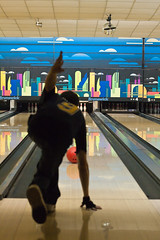 Young man after trowing an orange bowling ball