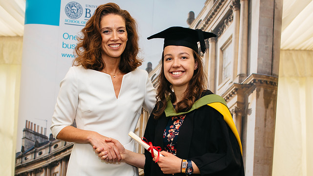 Madelaine in a gown with her degree certificate, shaking hands with a woman