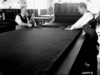 Men cut layers of cloth piled out and ready for marking patterns. / Des hommes coupent des bandes de tissu et les empilent, prêtes à être utilisées pour le marquage