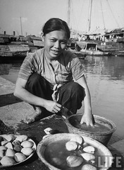 Saigon 1950 - A local woman selling oysters while peering into the distance