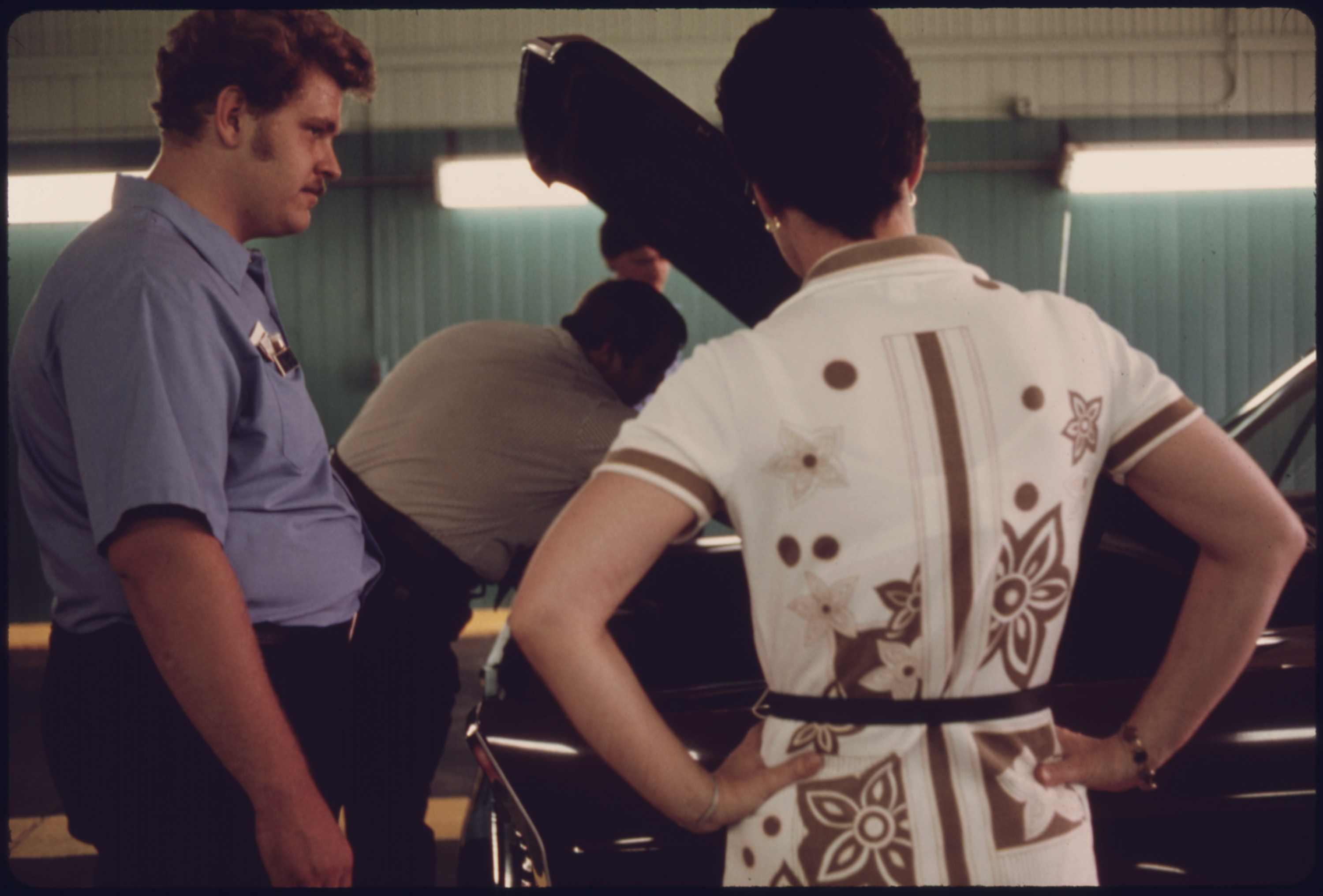 Unhappy Car Owner, Foreground, Watches as Public Works Department Employees Try to Locate the Reason Her Vehicle Failed Its Inspection for the Second Time at an Auto Emission Inspection Station at Norwood, Ohio...08/1975