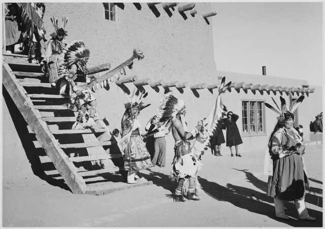 """Indians in headdress, male and female, descending stairs, """"Dance, San Ildefonso Pueblo, New Mexico."""""""