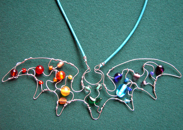 Rainbow Bat - a pendant in steel wire and glass beads