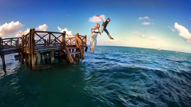 Wedding day at Dominicana - 16 p.m., sunset - bride and groom jump into the ocean