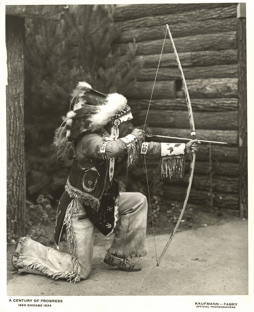 american indian demonstrating the use of a bow and arrow