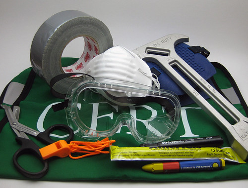Example of CERT gear given to students. Pictured: Reflective vest, duct tape, shears, safety whistle, glowstick, markers, gas shutoff tool, knee pads, dust mask.