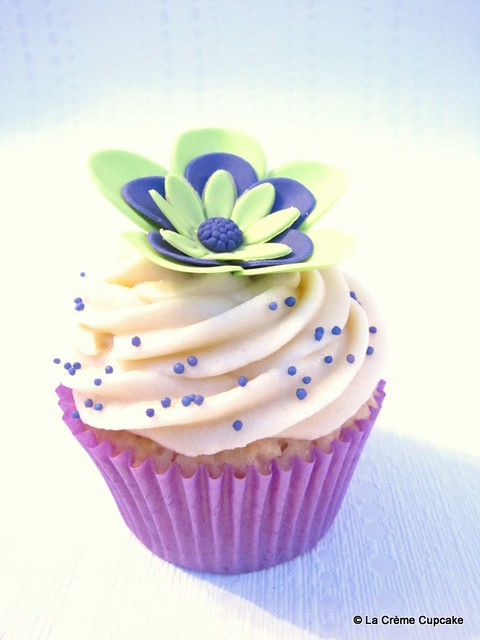 Vanilla cupcake decorated with lime green and purple flowers