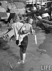 Saigon 1950 - A mother carrying her son and fish to a boat.