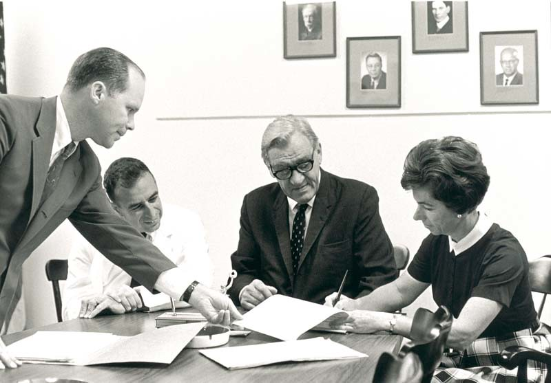 A group photo of Robert Joy Glaser (1918- ) with Cassius Kirk, John Ewart Wallace Sterling (1906-1985), and the Palo Alto mayor, sitting around a table signing documents