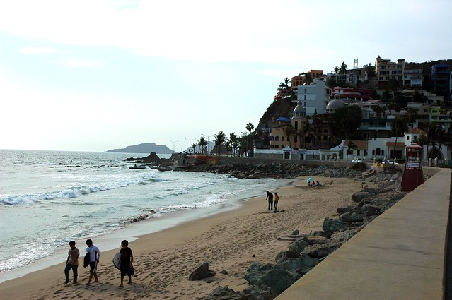 Strolling down the beach with surf boards, hanging out under an umbrella, South Mazatlan beach in the afternoon, beyond the seawall, Mexico