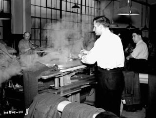 Men pressing Canadian Army uniforms in large clothing factory. / Hommes pressant des uniformes de l'Armée canadienne dans une grande usinede vêtements