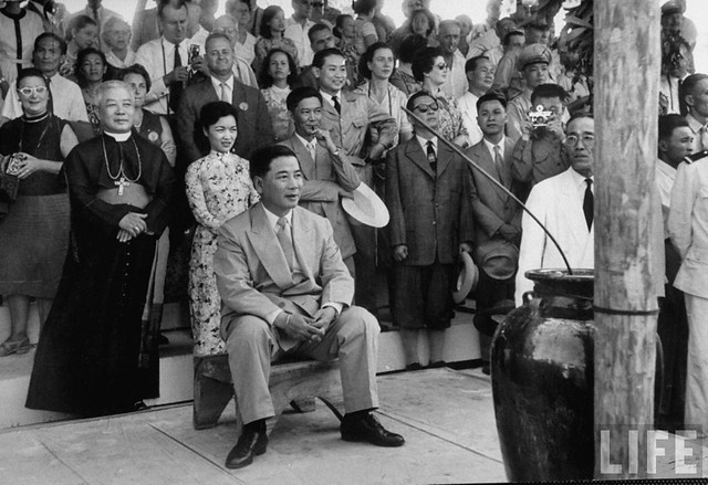 1957 - Vietnamese President Ngo Dinh Diem (seated) and his brother Bishop Ngo Dinh Thuc (L) attending a program held during New Year celebration in the central highlands.