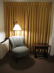 A corner of a room with a chair, light, and table, intended as a reading nook.