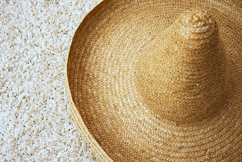 Large straw sombrero with twisted tip on carpet