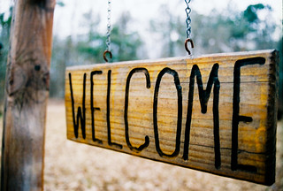 Wooden sign, hung from a wooden bracket with silver chains. The word Welcome is burned into the sign.