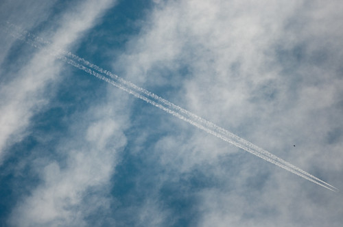 White plane trail on a cloudy sky