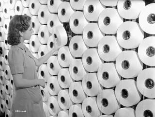 """Woman worker replaces a spool of cotton yarn on a """"warping machine"""" at the Montreal Cottons textile plant. / À la manufacture de textiles de la Montreal Cottons, une ouvrière remplace une fusette de fil de coton sur un « ourdissoir »"""