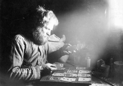 Charles Ainsworth playing cards inside cabin at 60 Above on Sulphur Creek, Yukon Territory