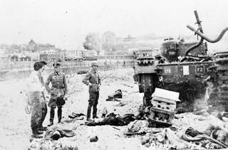 German Officers standing on Dieppe beach among Canadian dead and wounded / Officier allemand debout parmi les soldats canadiens morts et blessés