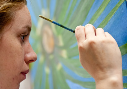 Newman University student paints during art class