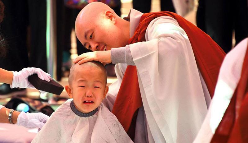 Seorang samanera kecil menangis saat dicukur rambutnya oleh seorang bhiksu di upacara penahbisan samanera sementara di Vihara Jogye, Seoul, Korea Selatan