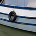 Small photo of Car tire hanging on the side of a fishing boat