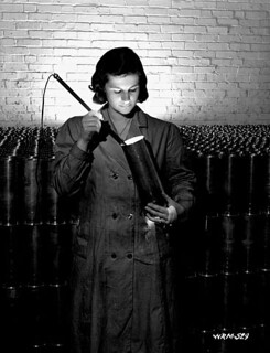 Female munitions plant worker inspecting the interior of a 25-pounder field gun case, Montreal, Que., March 1941 / Ouvrière d'une fabrique de munitions qui examine l'intérieur d'une douille d'obus pour canon de 25 livres, Montréal, Qc, mars 1941