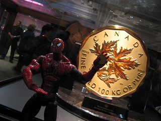 Spider-Man holding a loonie ($1) in front of the one million dollar coin  (during the Vancouver 2010 Olympics)