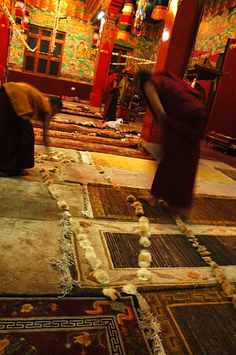 Flower (Seed pods) strung together to decorate Tharlam Monastery are arranged on the floor on Tibetan carpets prior to hanging by monks, for Bodhisattva Day, Boudha, Kathmandu, Nepal by Wonderlane