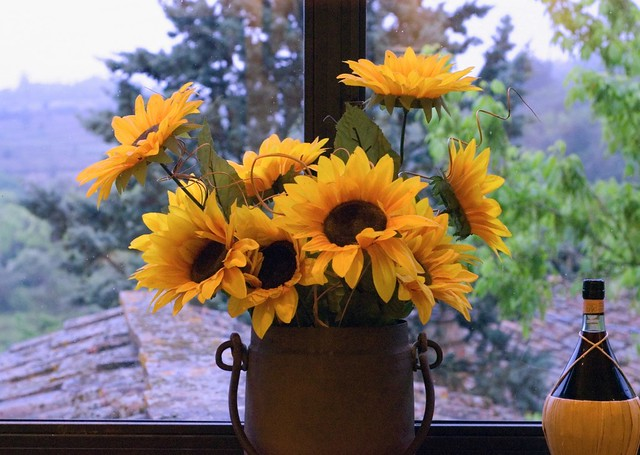sun flowers, a red, and the tuscan hillside