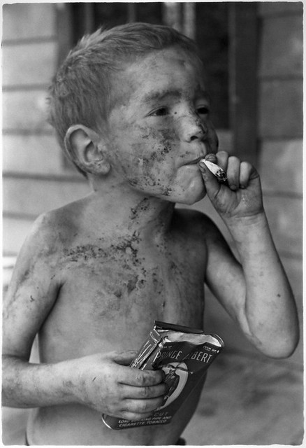 Boy covered by dirt smoking cigarette with one hand, holding can of tobacco in other, Kentucky, 1964, by William Gedney