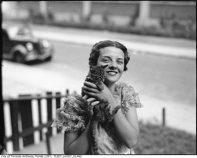 Billie Hallam, Miss Toronto 1937, posing with a kitten, in front yard of her home, 191 Booth Avenue