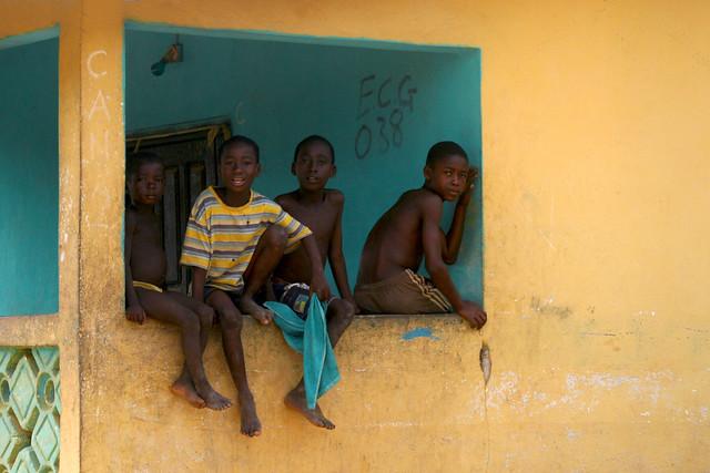 Kids sitting on a balcony in Ghana.