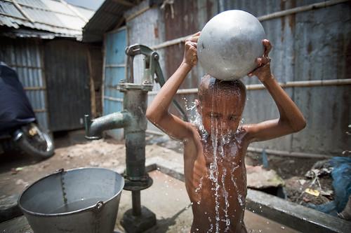 孟加拉達卡一處貧民窟,孩童正用抽地下水來盥洗。(Source: UN Photo/Kibae Park via Flckr)