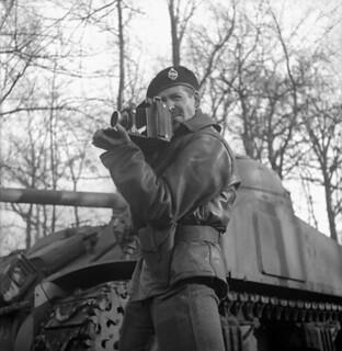 Lieutenant H. Gordon Aikman of the Canadian Army Film and Photo Unit, holding an Anniversary Speed Graphic camera. / Le lieutenant H. Gordon Aikman, de l'Unité de film et de photo de l'Armée canadienne, tient un appareil-photo Anniversary Speed Graphic