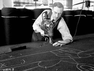 Man cutting through numerous layers of khaki cloth in pattern of chalk-outlined Canadian army uniform, Dec. 1939 / Un homme faisant une coupe dans plusieurs couches de tissu kaki le long d'un patron d'uniforme canadien tracé à la craie, déc. 1939