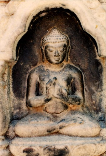 Buddha statue in niche with evidence of offerings, hands in teaching and intellectual discussion, or argument without fear, legs in the lotus position, Boudha, Kathmandu, Nepal by Wonderlane