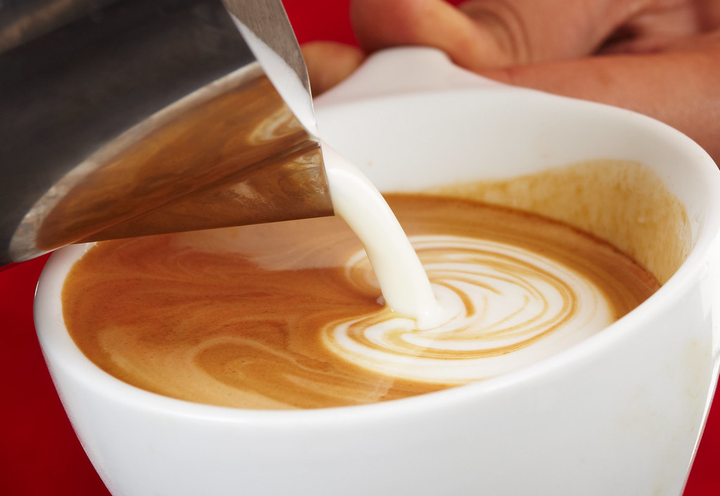 Feathery flowering flow of the steamed milk into espresso
