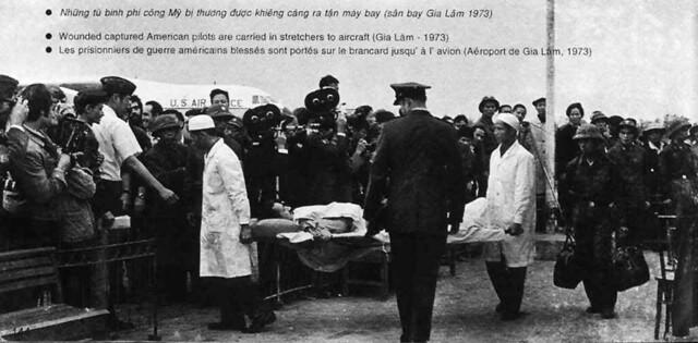 H103 Những tù binh phi công Mỹ bị thương được khiêng cáng ra tận máy bay (sân bay Gia Lâm 1973).
