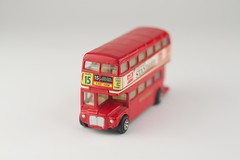 soft drink(0.0), carbonated soft drinks(0.0), coca-cola(0.0), brand(0.0), model car(1.0), vehicle(1.0), red(1.0), double-decker bus(1.0), bus(1.0), toy(1.0),