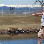 With snow-capped peaks of the Rockies as a backdrop, Chris Zagone unleashes a drive at Spring Fling 2005 at Expo Park.