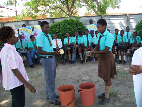High school students demonstrating using soap for handswashing to combat cholera after using toilets while Y2Y member looks on