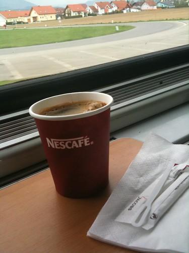 Photo Zugfahrt, Kaffeebecher mit Nescafe auf der Ablageflaeche