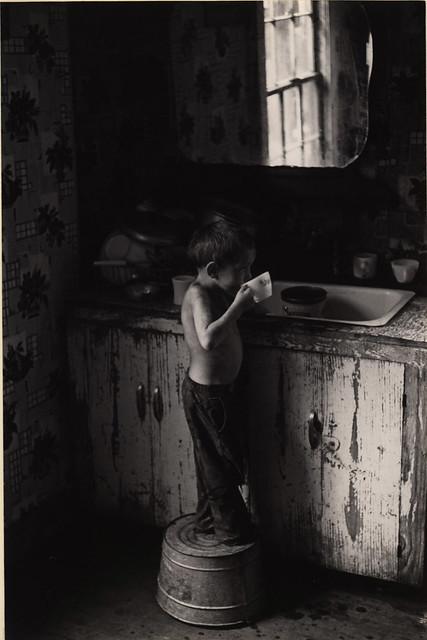 Boy standing on washtub and drinking by kitchen sink, Kentucky, 1964, by William Gedney