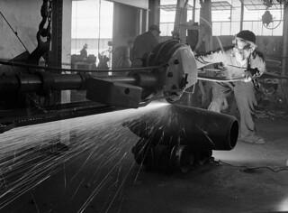 Workman wearing protective goggles, mask and clothing, sawing the body of a bomb at the Cherrier plant, May 1941 / Ouvrier portant lunettes, masque et vêtements de protection en train de couper le corps d'une bombe à l'usine Cherrier, mai 1941