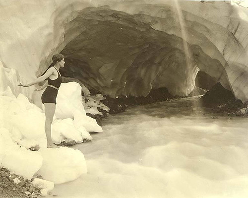 Woman in bathing suit at edge of stream near Paradise Glacier ice cave, Mount Rainier National Park